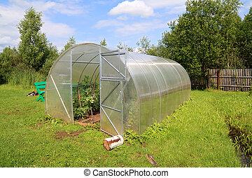 plastic hothouse in summer garden