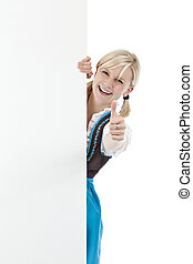 Beautiful blond girl in dirndl shows thumb, holding blank billboard. Isolated on white background.