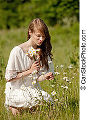 A young, beautiful lady picks flowers on a summer meadow