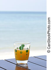 Glass of orange juice at the beach - A glass of orance juice...