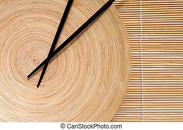 japanese chopsticks in wooden round dish on bamboo placemat...