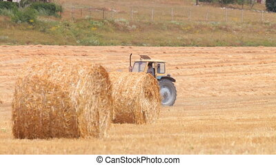 Tractor and Hay Bale - Tractor and hay bale in a cut field