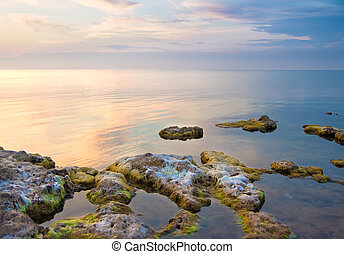 Sea and rock at the sunset. Seascape composition.