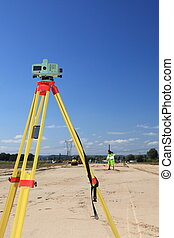 geodesist taking measurement - Builders level - construction...