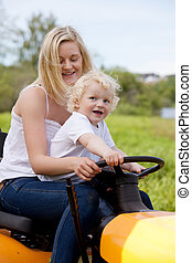 Mother Driving Tractor with Son - A mother driving a lawn...