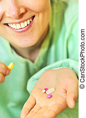 Woman holds pills in a hand