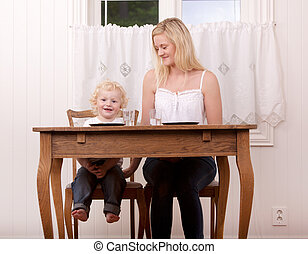 Mother and Child at Table - A happy smiling mother and child...