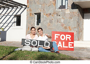 For Sale Home / Sold - Couple holding sold sign and keys...
