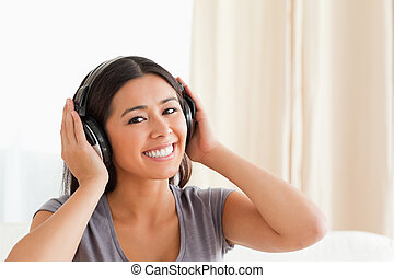 close up of a charming woman with earphones looking into camera