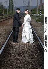 New begining - Newlyweds walking together on the raylway and...