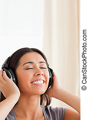 close up of  a smiling woman with closed eyes and earphones