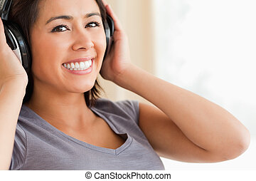 close up of smiling woman sitting on sofa with earphones looking into camera in livingroom