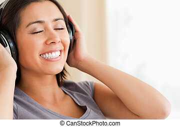 close up of smiling woman sitting on sofa with earphones and eyes closed in livingroom