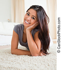 charming woman lying on a carpet in livingroom