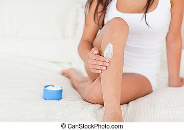 goodlooking woman putting cream on her legs in bedroom