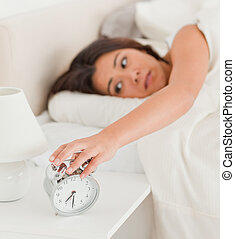charming woman waking under sheet turning off alarm clock in...