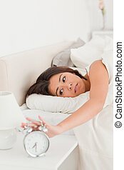 gorgeous woman waking under sheet turning off alarm clock in...