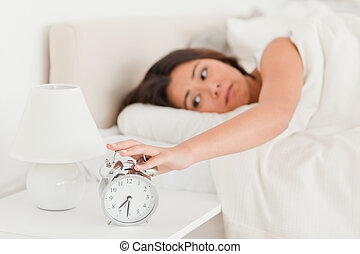 cute woman waking under sheet turning off alarm clock in...