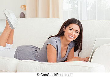 cute woman lying on sofa with notebook in front of her smiling into camera in livingroom