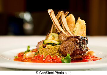 Grilled lamb served on cous-cous with sun dried tomatoes and...