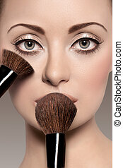 Portrait of a beautiful woman with a make up brush - On a...