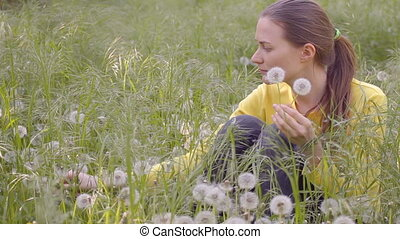 Young woman plucking dandelions on