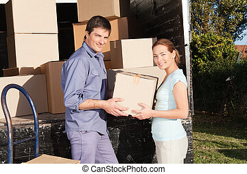 Happy Couple Moving Boxes - Smiling couple moving luggage at...