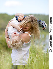 Mother and Son Playing in Meadow - A mother and son playing,...