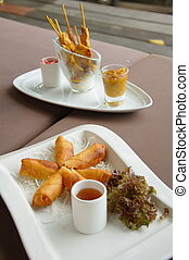 Spring rolls and chicken satay plates - Spring rolls on a...