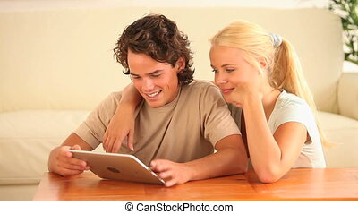 Couple using a tablet computer in a living room
