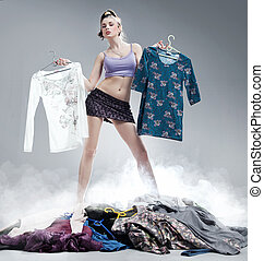 Portrait of pretty young woman choosing new clothes and...