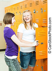 Teenage Girls Gossip by Lockers - Two teenage girls talking...
