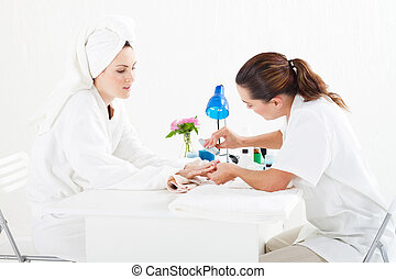 beautician applying manicure - female beautician applying...
