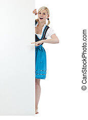 Young surprised woman in dirndl pointing with finger at blank sign. Isolated on white background.