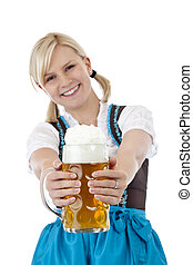 Young blonde woman with dirndl toasts with beer...