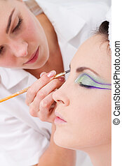 professional female makeup artist applying makeup to...