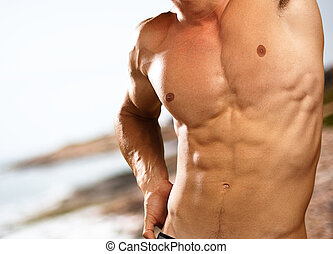 muscle man on a beach background