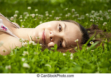 beautiful young woman smiling on grass field - A very...