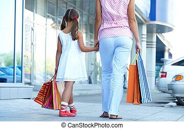 Shopping with mother - Rear view of a woman and girl with...