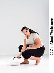 overweight woman smash scale with a hammer