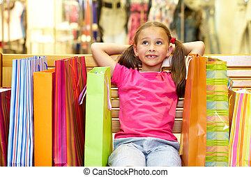 Happy shopper - A little girl sitting on bench with plenty...