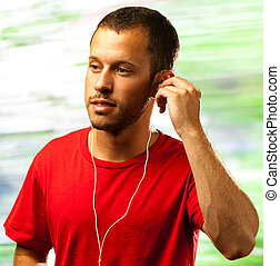 man listening to music with earphones on a nature background