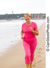 senior woman jogging on beach