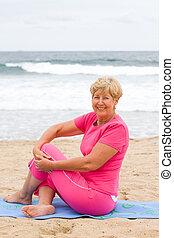 senior woman stretch on beach