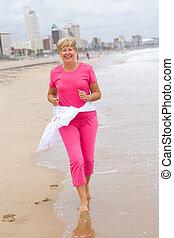 senior woman running on beach