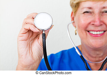 Senior female doctor holding stethoscope toward you by copy...