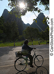 Yangshuo - Chinawoman on bicycle in Yangshuo
