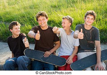 happy teen boys - group of teen boys resting on playground...