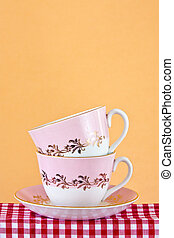 Two retro style teacups on gingham cloth