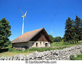 House and wind turbines - Small house made of wood and white...